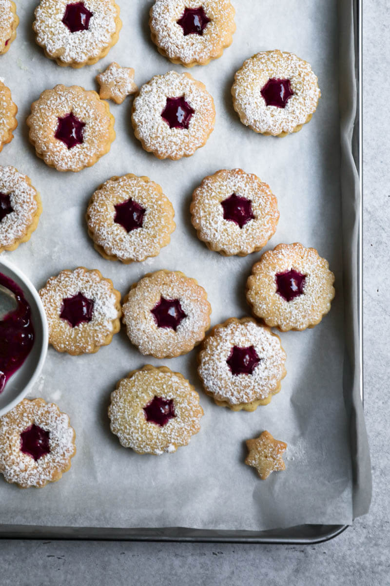 Raspberry linzer cookies on a baking tray lined with parchment paper