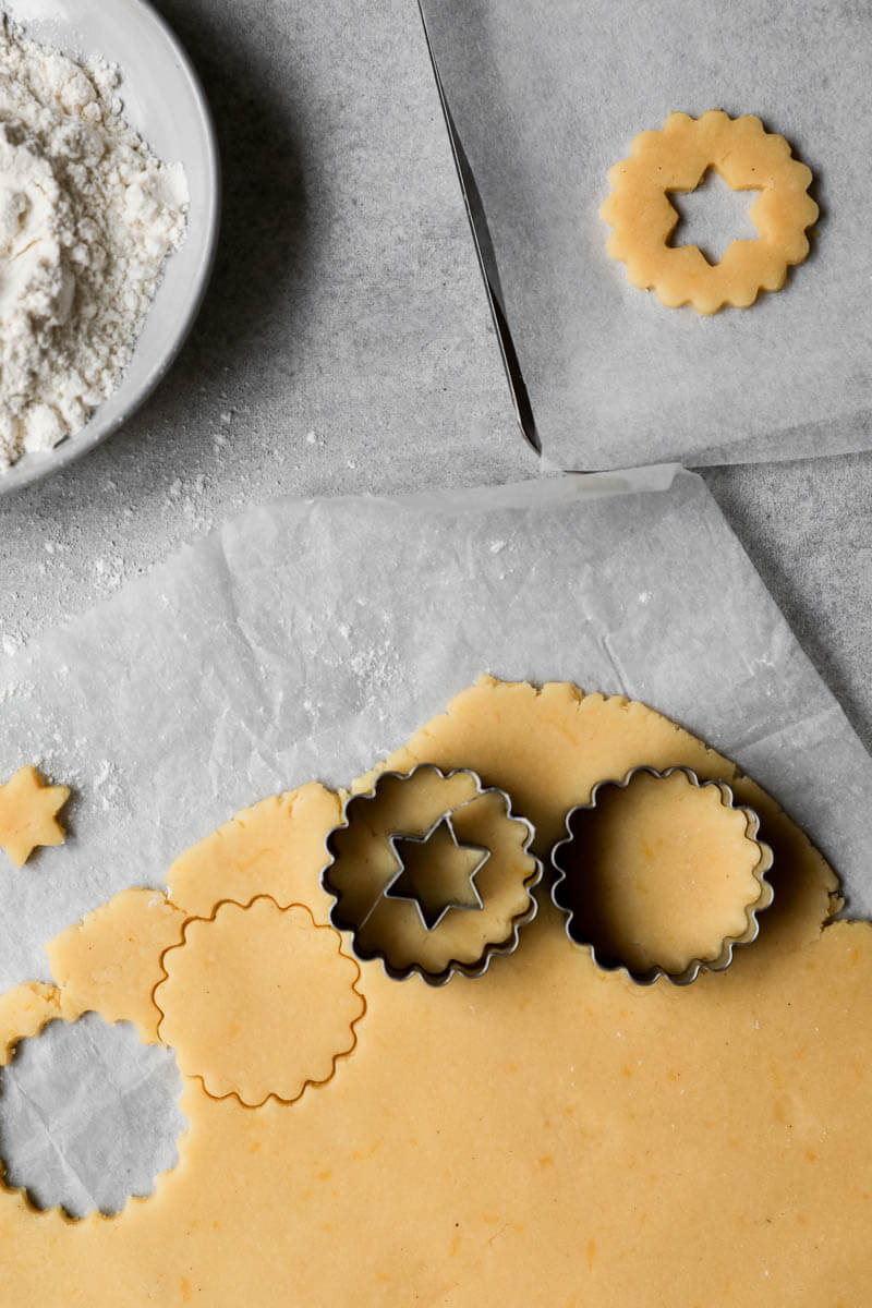 Rolled out linzer cookie dough with cookie cutter on top