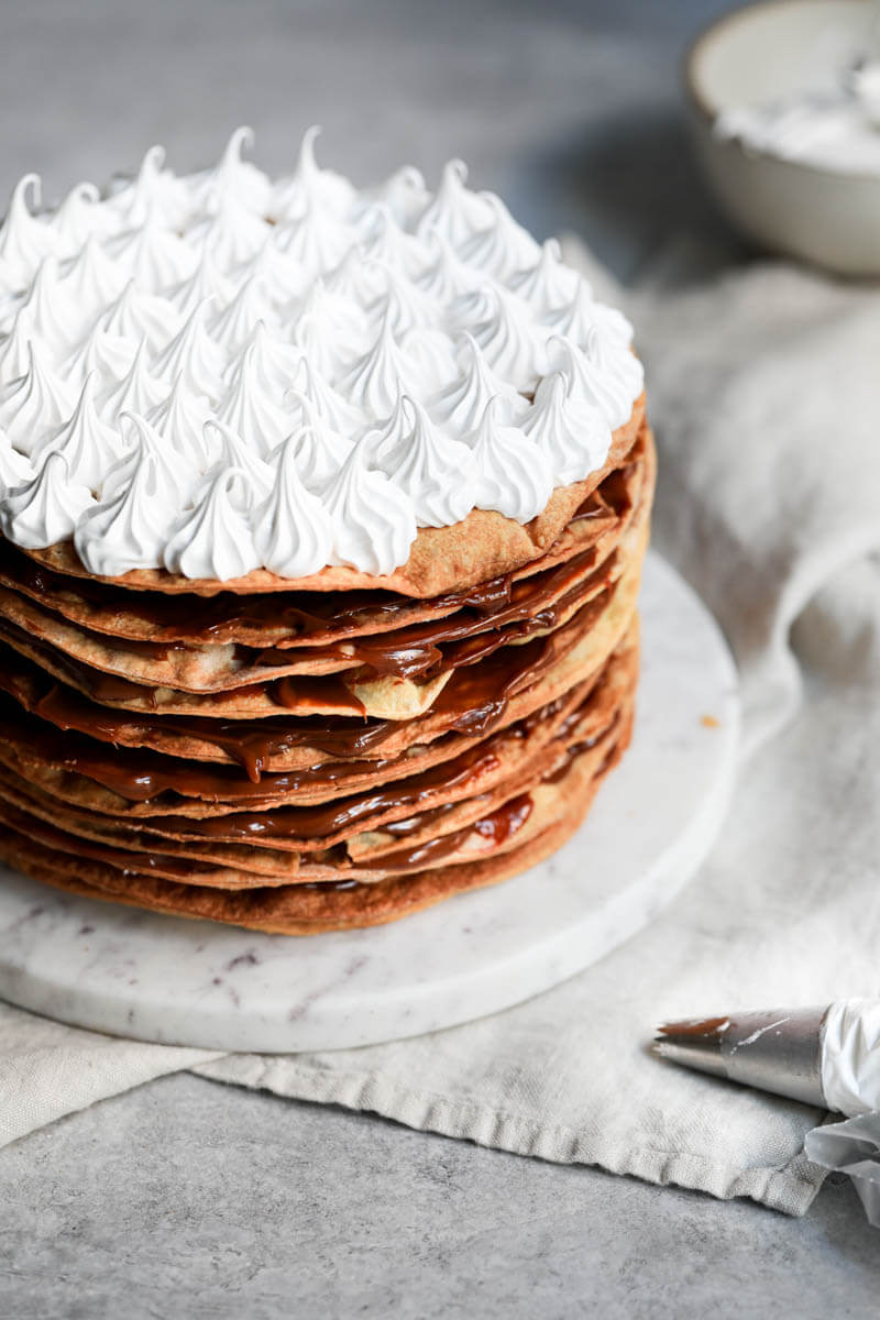 ¾ of the rogel cake on a marble plate over a linen with a piping tip in the bottom right corner