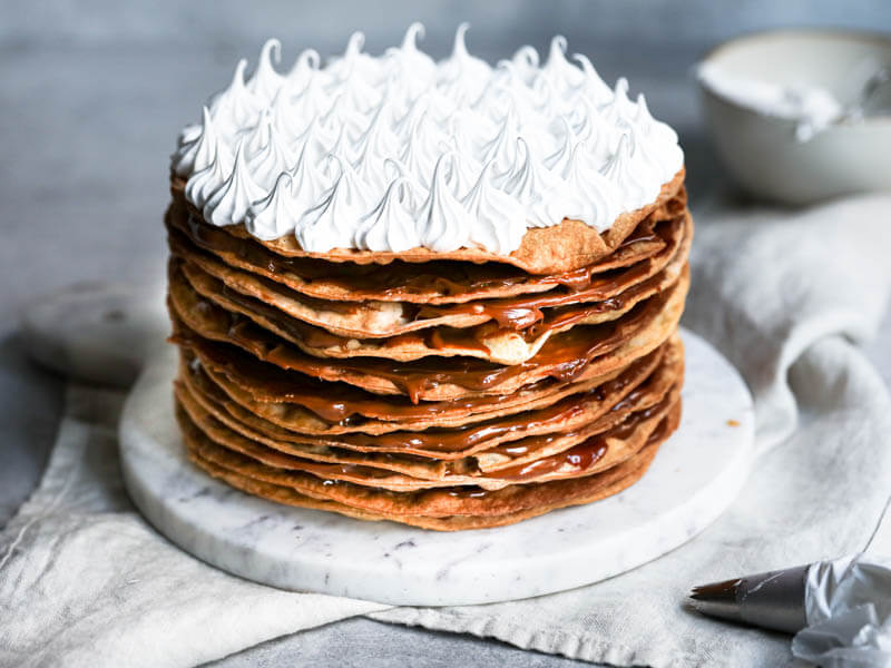 Whole rogel cake frosted with swiss meringue with a bowl behind it out of focus