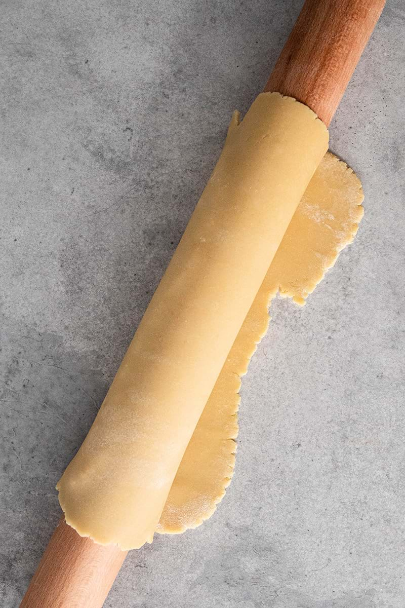 Rolled out shortbread crust rolled around the rolling pin
