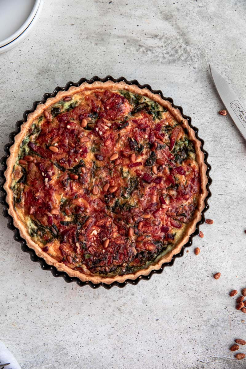 Baked spinach bacon quiche in the quiche tin.