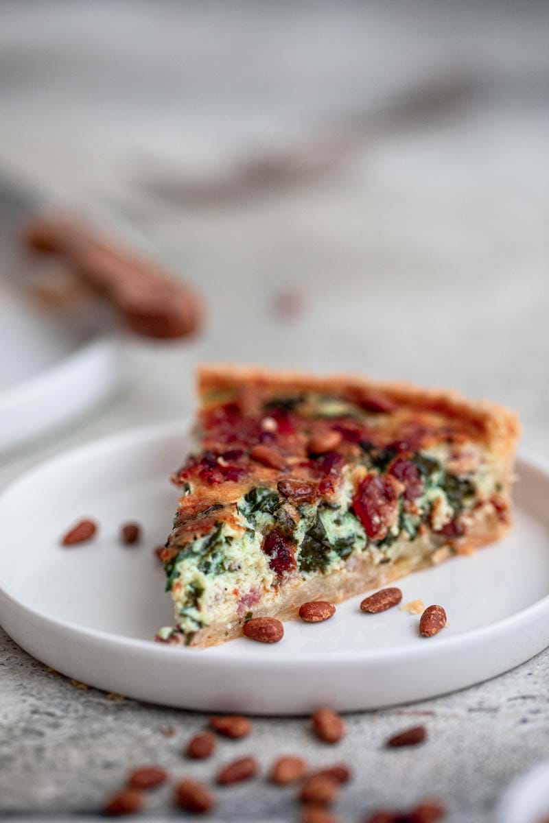 Close-up shot of one slice of the spinach bacon quiche.