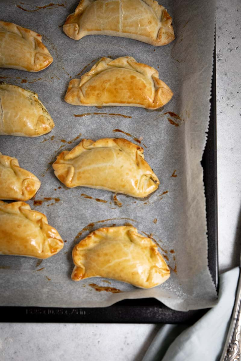 Overhead shot of the baked empanadas on a piece of parchment paper