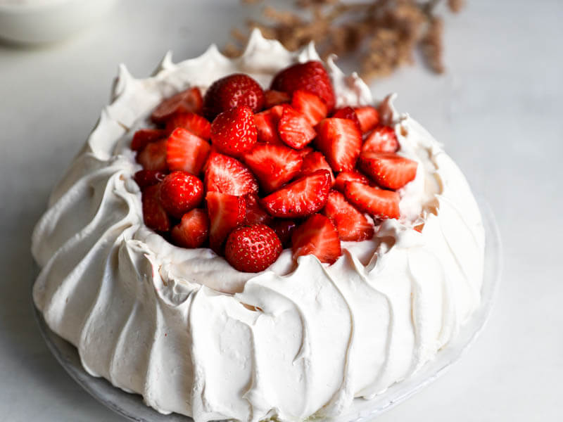 45° shot of the strawberry pavlova served on a white plate with flowers on the background