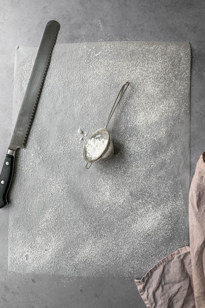 A piece of parchment paper sprinkled with powdered sugar with a strainer and a serrated knife on the side.