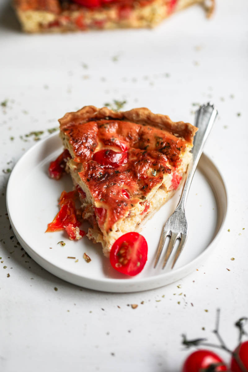 45° shot of one slice of tomato quiche on a plate