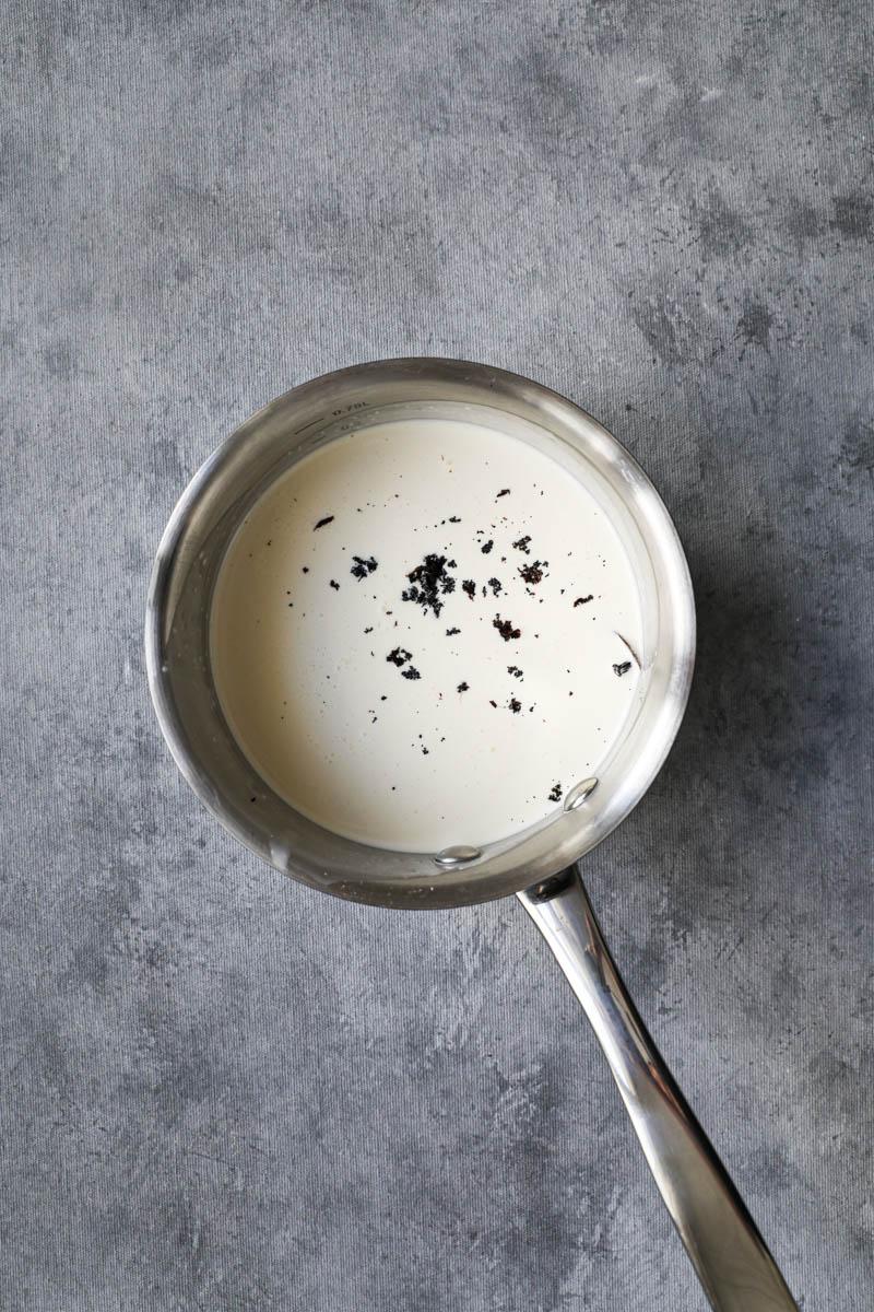 A small pan with cream and a scarped vanilla bean ready to start making vanilla bean crème brûlée.