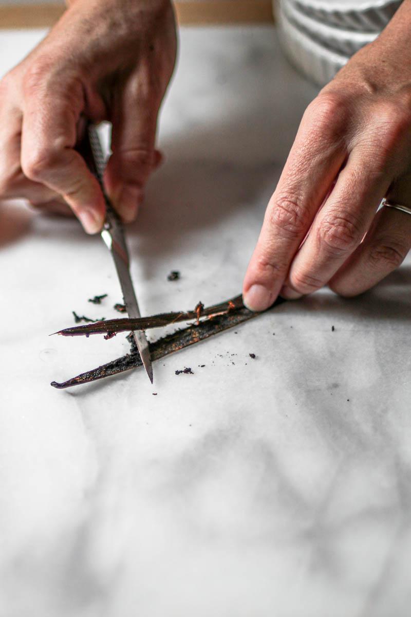 2 hands scraping a vanilla bean using a small paring knife.