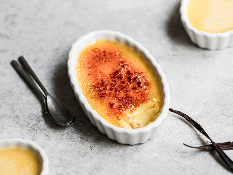 Vanilla bean creme brûlée, baked and torched, in an oval ramekin, with another crème brûlée behind it and 2 small spoons on the side.