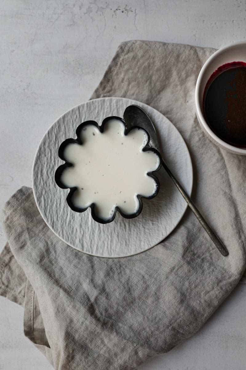 Panna cotta chilled and ready inside the mould placed on white plate on top of a beige linen cloth.