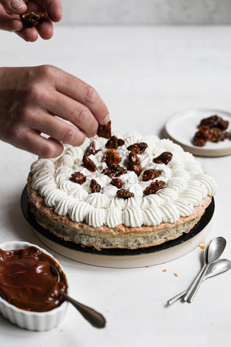 Assembling the walnut dacquoise cake: one hand placing the caramelized walnuts on top of the Chantilly cream frosting.
