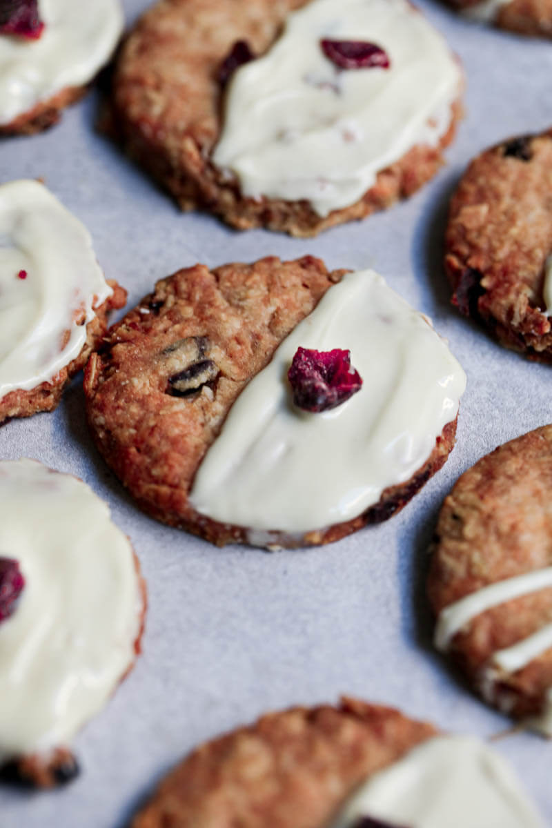 Oatmeal cranberry cookies frosted with white chocolate surrounded by other cookies