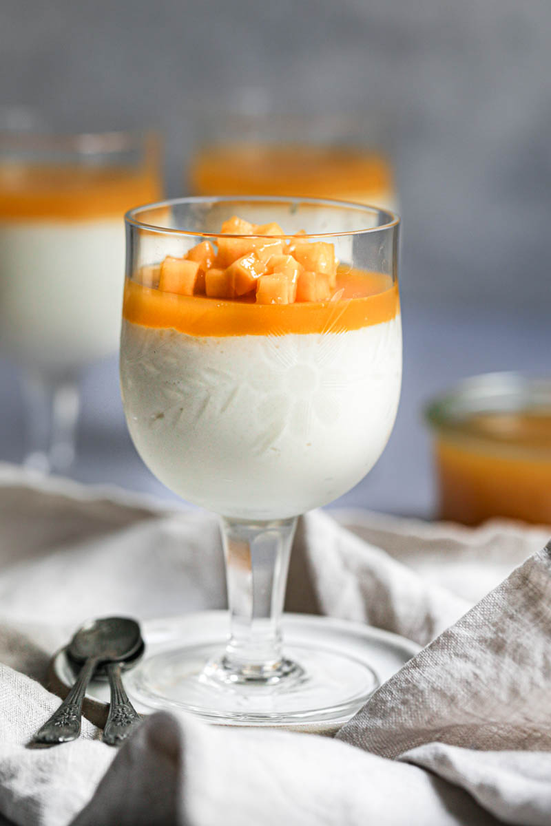 1 wine glass filled with white chocolate mousse and fresh mango and mango jelly on a small white plate with 2 spoons on the side and placed on a beige linen.