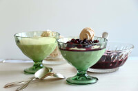90° shot of the white chocolate mousse topped with blueberry sauce and fresh meringues served on green glass cups