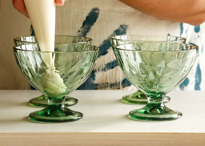 Filling the glasses with the white chocolate mousse using a pipping bag