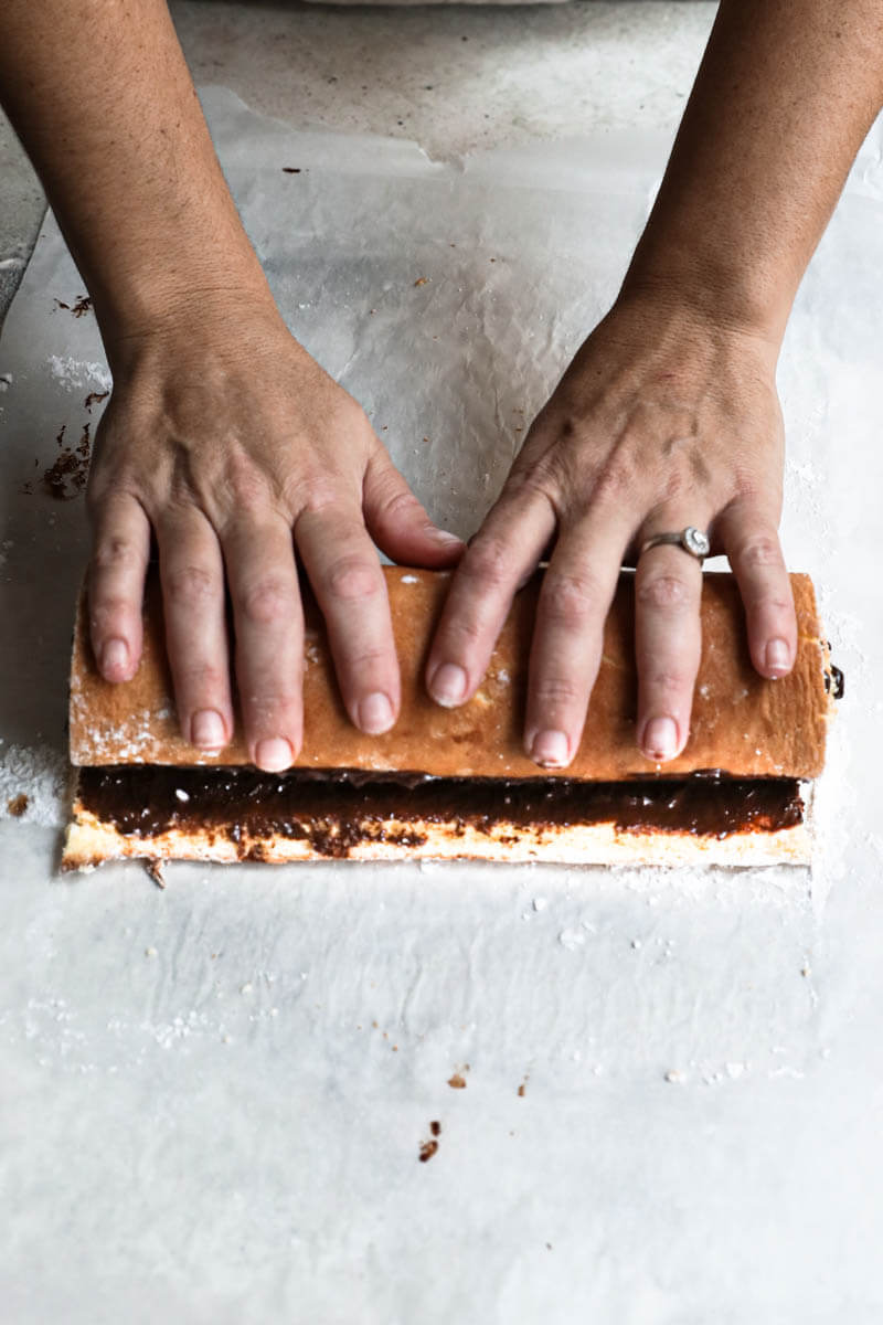 Two hands rolling the filled cake