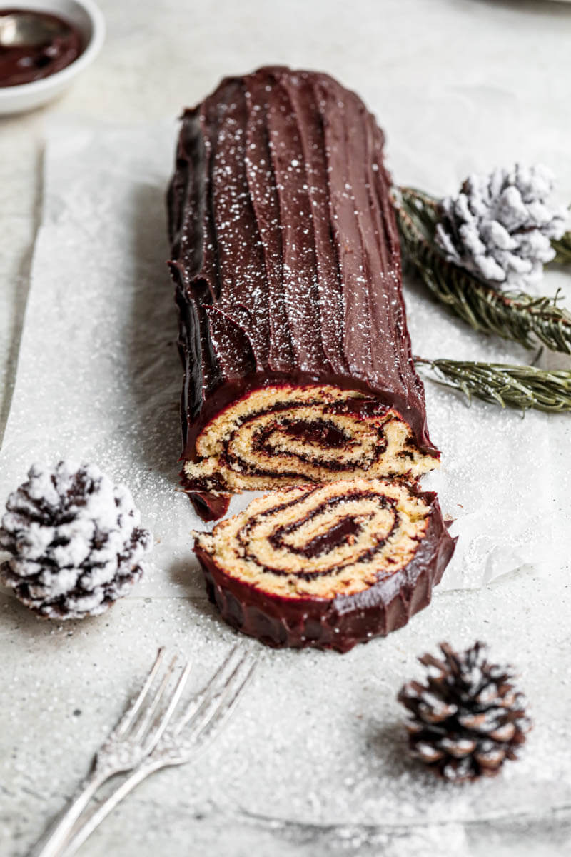 Yule log cake with some pine cones laying around