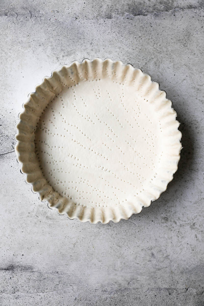 The tart tin lined with the quiche crust ready to bake.