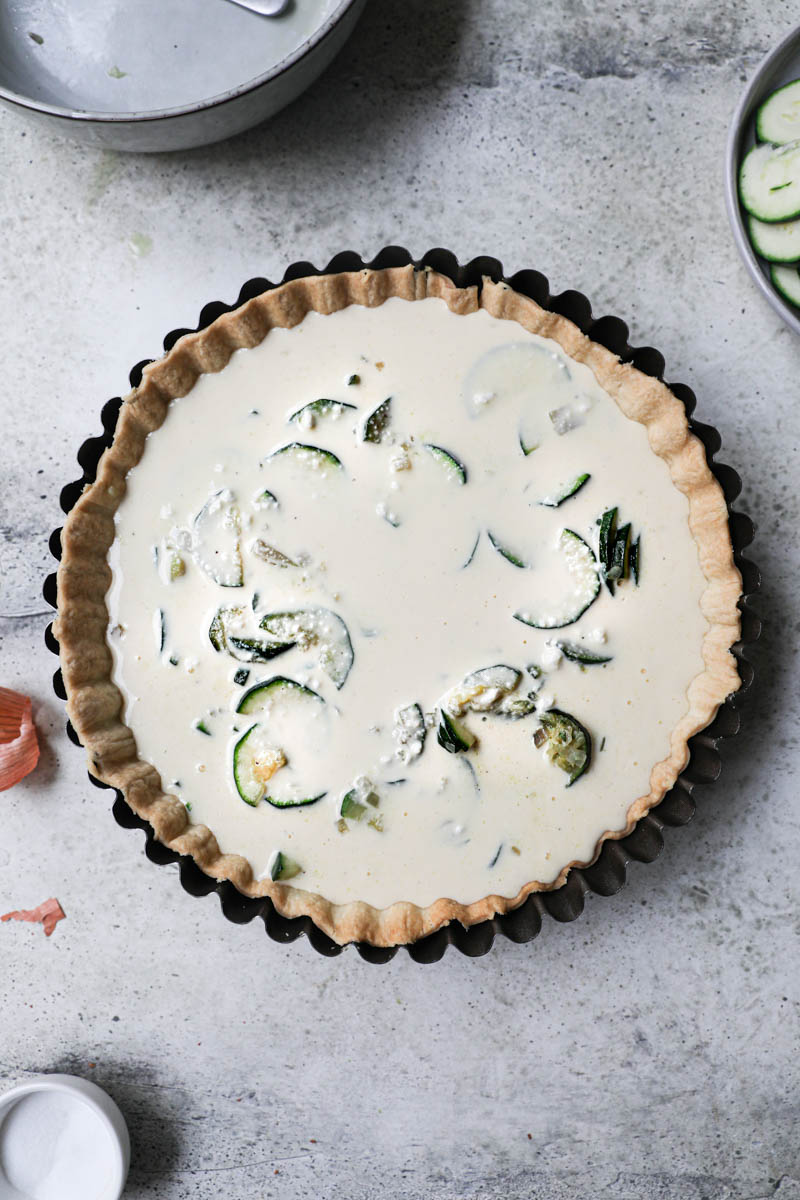 The blind baked quiche crust filled with the cooked zucchini and shallots covered with the quiche batter with some plates and bowls on the side.