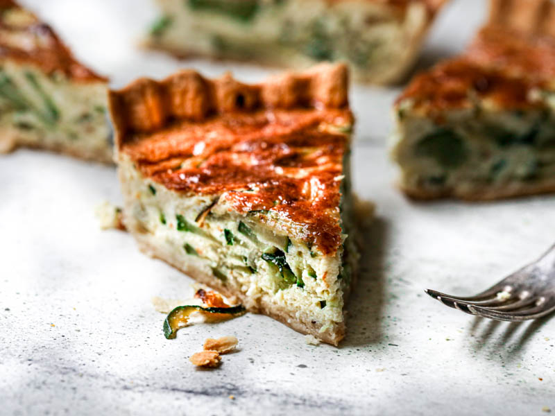 A slice of zucchini quiche with other sliced blurry in the back and a fork on the side.