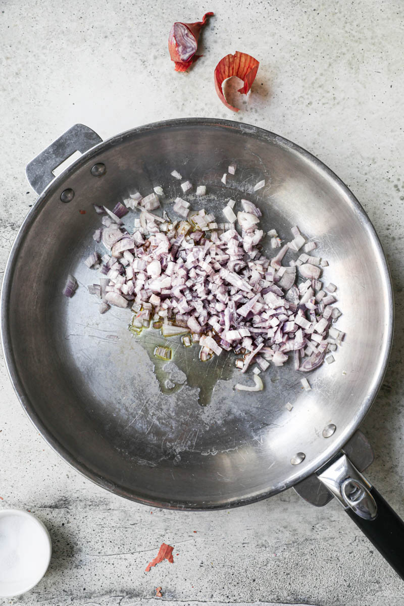 Chopped shallots on a pan with a dollop of olive oil.